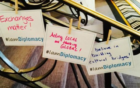 Handwritten signs incorporating the #IAmDiplomacy hashtag
