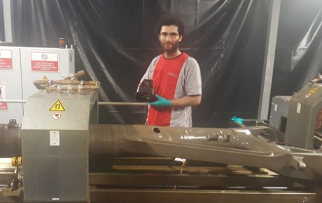 Man standing behind a landing gear with an ultraviolet light