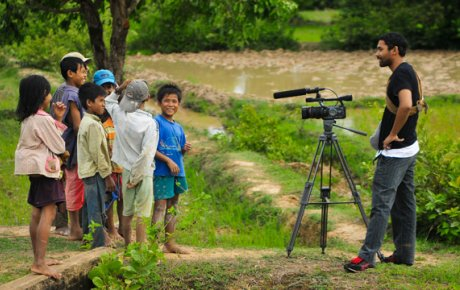 Man stands in front of group of young Cambodian children with video camera on tripod.