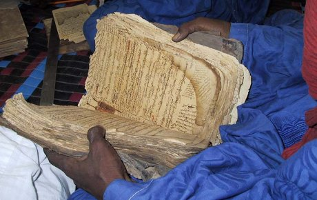 Close up of a very large and old book being held opened, the pages are wrinkled and tainted yellow