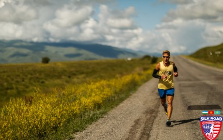 Dean running under a sunny sky next to yellow flowering fields