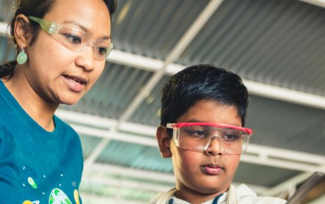 Woman wearing construction goggles stands beside young boy also wearing goggles, both looking at an object