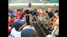 Cal Ripken huddles with young baseball players.