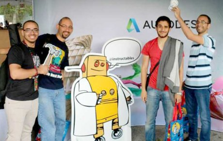 Men holding up with drawings and standing next to Robot poster
