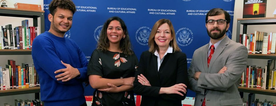 Assistant Secretary stands in the middle of young adults smiling with arms crossed