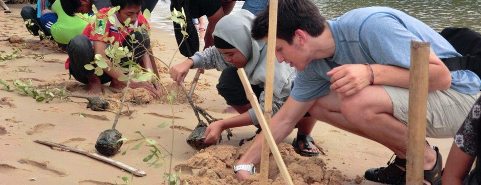Justin, of Connecticut, plants mangroves with Indonesian students.