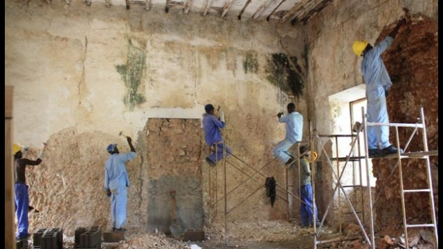 Workers remove old lime plaster from the walls of an 18th-century building on Mozambique Island.