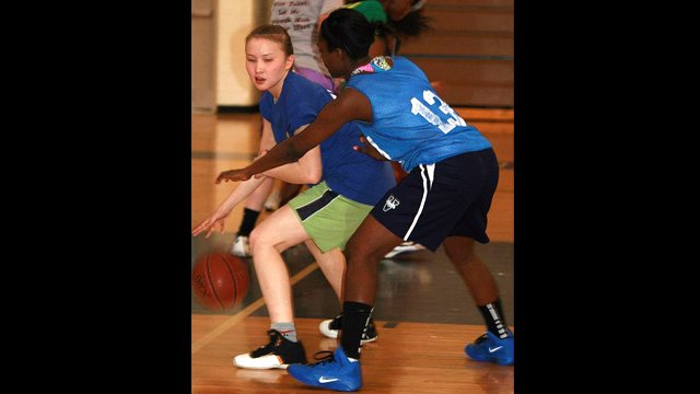Balgyn from Kazakhstan dribbles as her American peer guards her.