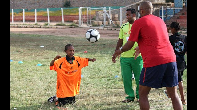 Tony Sanneh works on header techniques with a young Ethiopian.