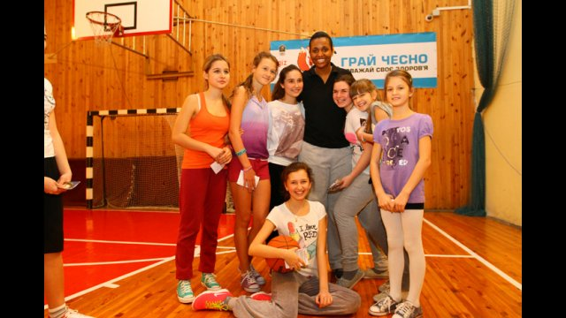 Girls from Ukraine pose with Tamika Raymond before a fast-paced basketball clinic.