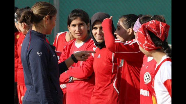 "Sports Envoy Lorrie Fair gives a ""pep talk"" to members of the Afghan Women's National Soccer Team."