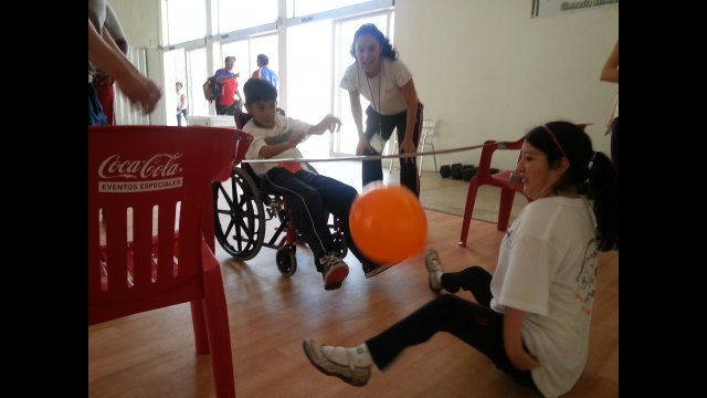 A girl with arthrogryposis practices her sitting volleyball with a teammate