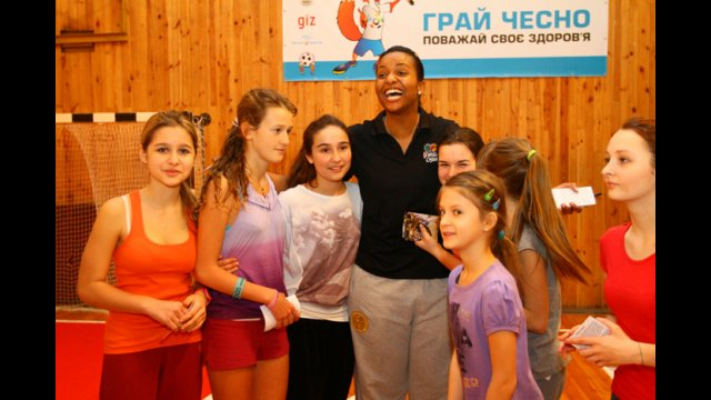 After autograph time, Tamika Raymond has fun with young Ukrainian basketball players.