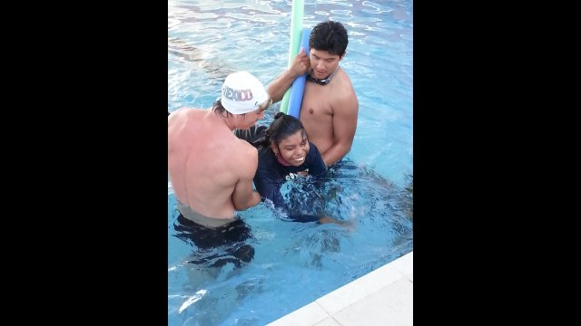 A young girl with cerebral palsy enjoys a swimming class