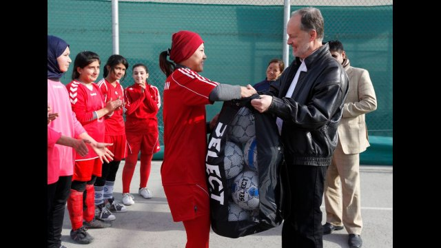 Ambassador James Cunningham with a member of the Afghan Women's National Soccer Team.