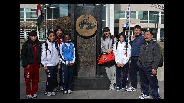Mongolian wrestlers pose at the Olympic Truce statue in Colorado.