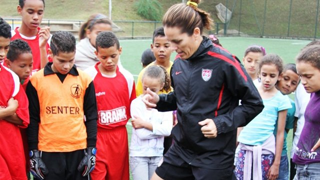Julie Foudy demonstrates some of her favorite warm-up moves to a group of youth participants during a training clinic near São Paulo.