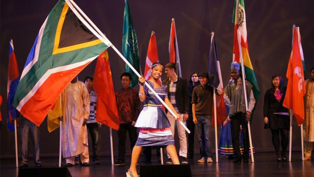 Girl in festive attire walks across stage holding a large South African flag