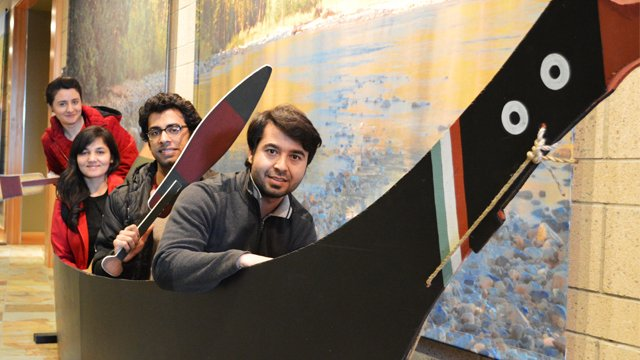 Several young people in a display boat in what looks like a museum