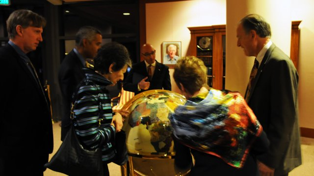 Jay Hakes (at far right), Director of the Carter Center Library and Museum shows Board Members a globe on display in the Center. He explained that each country on the globe is made with indigenous materials from that country.