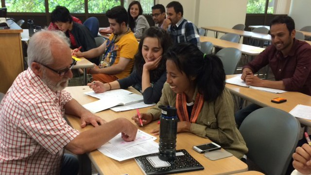 Older man explaining something to students