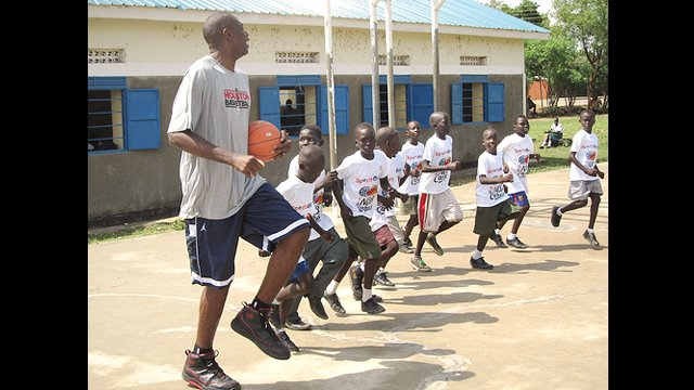 The boys try to keep up with the NBA star Dikembe Mutombo during practice.