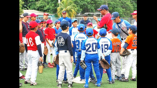 Young players cluster to hear Barry Larkin's baseball tips in Guayaquil, Ecuador.