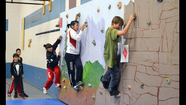 Mongolian wrestlers try out a climbing wall with students during their visit to an elementary school in Parker, CO.