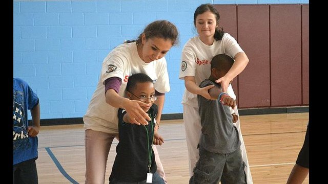 The coaches practice what they learned in a youth sports development session with kids from a local Boys and Girls club
