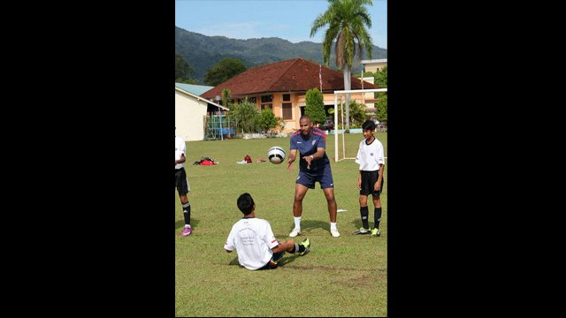 Sports Envoy, Tony Sanneh, tosses a ball to a young Malaysian player.