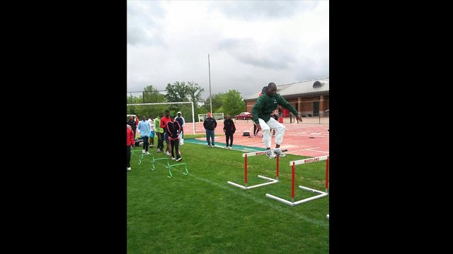 The participants practice different track and field events including shot put and hurdles.