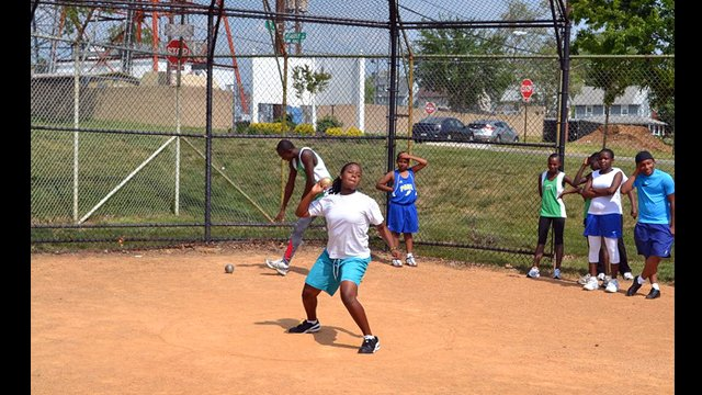The participants practice their shot put skills.