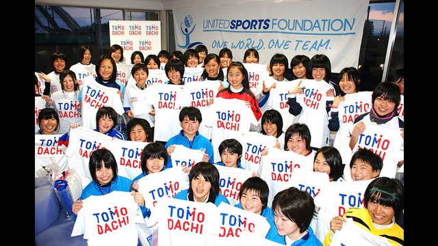 "These young girls hold up their ""TOMODACHI"" shirts to represent the initiative to strengthen the friendship between Japan and the U.S."