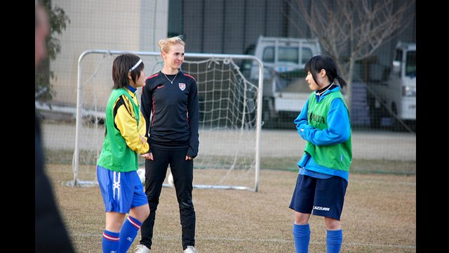 U.S. defender Heather Mitts discusses strategy techniques with her young Japanese teammates.