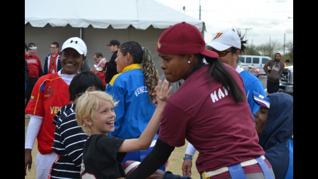 The young coach visitor high-fives a young American emerging athlete.