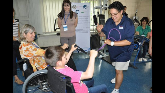American participant works with youth to demonstrate strength training techniques during a workshop with sport coaches in Gyumri.