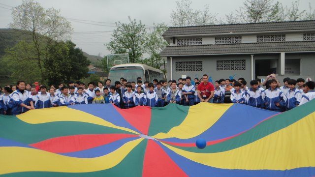 Chinese youth enjoy playing a parachute game with the Americans.