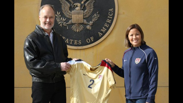 Sports Envoy Lorrie Fair presents Ambassador James Cunningham with a jersey.