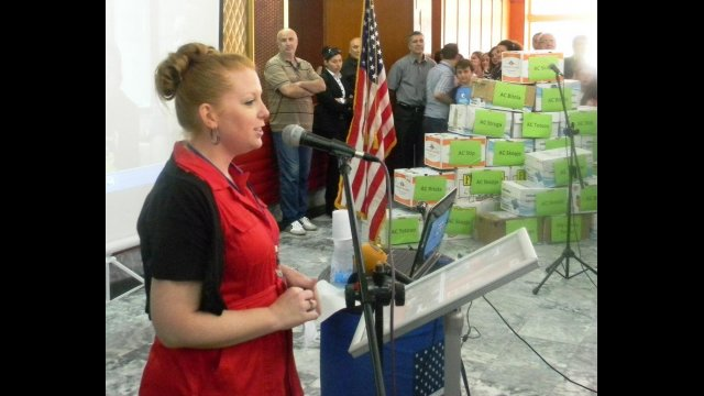 Fulbright English Teaching Assistant Jennifer Birdsall speaking at the American Corner Tetovo, where the 14,500 English books collected through donations were distributed. The pyramid of books can be seen in the background.