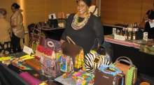 Women wearing African print dress stands behind a desk full of African print purses and accessories