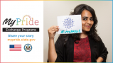 Smiling Indian woman holding up a hand-draw sign with a mandala and #MyPride written on it