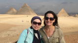 Two women pose in front of Egyptian pyramids