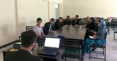 Group of young adults sit around a table in a classroom
