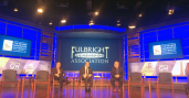 Three men sit on stage with Fulbright Association graphic on screen in background