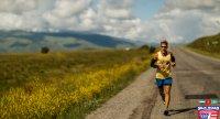 Dean running under a sunny sky next to yellow flowering fields