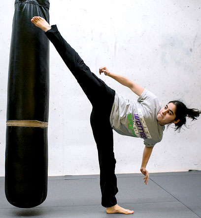 Girl kicking high onto a punching bag
