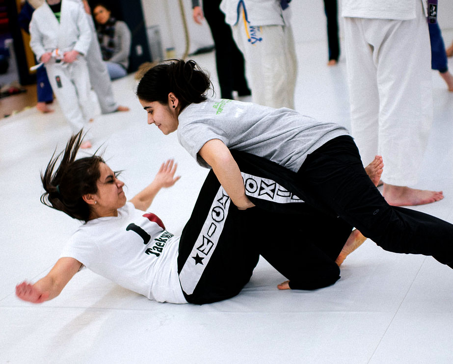 Two girls fighting, one is pinning the other to the ground