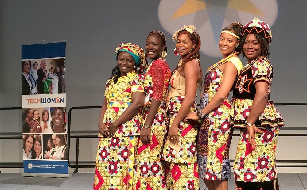 Women participants pose for a picture near TechWomen sign