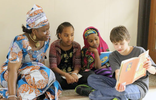 Woman participant sitting with four kids reading a book
