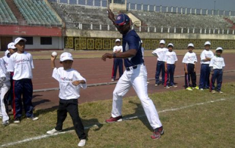 Joe Logan assists team members with their fast pitch.